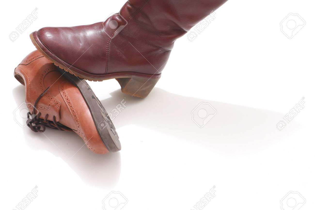 Domination Symbolized By Shoes On White Background Stock Photo 1300x866