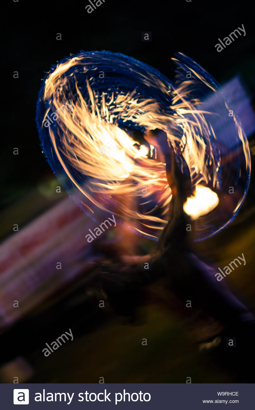 Motion blurred night shot showing a fire eater jugglers torches 866x1390