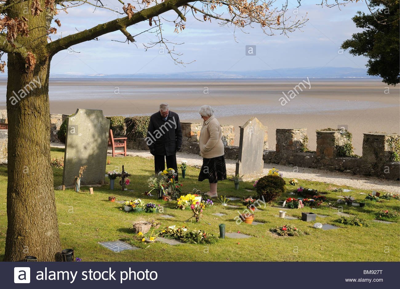 Elderly couple grieving at graveside in graveyard of St Cuthberts 1300x940
