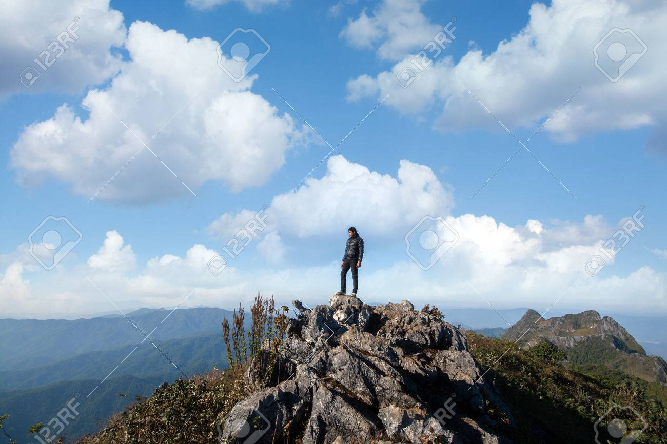 Mountain Top With Young Southeast Asian Man In Blue Sky And Clouds 1300x866