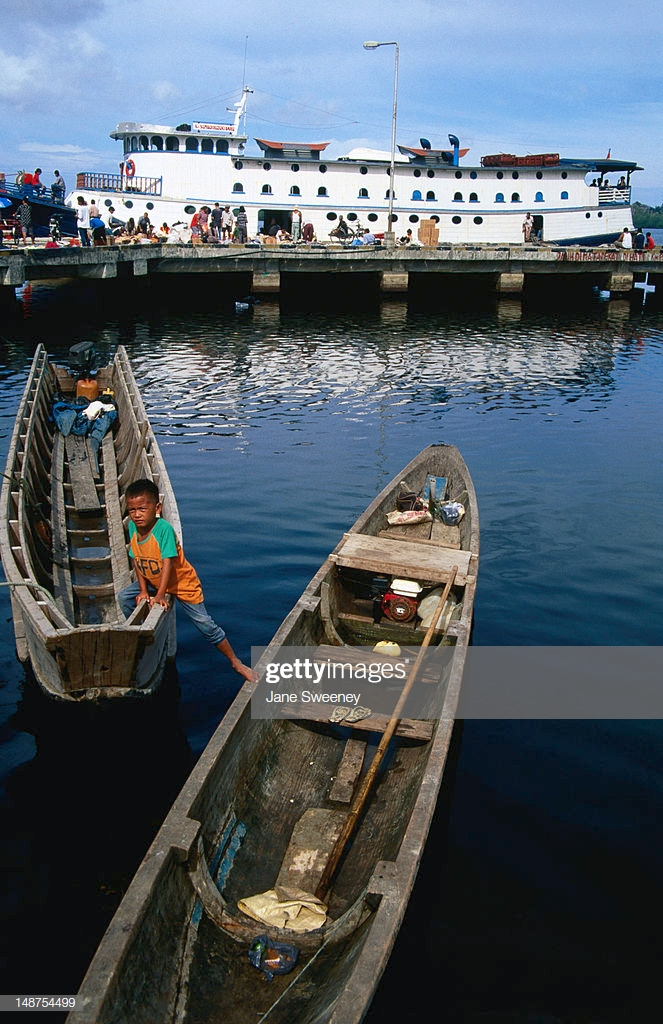 Boy In Dugout Canoe With Padang Ferry In Background Stock Photo 663x1024