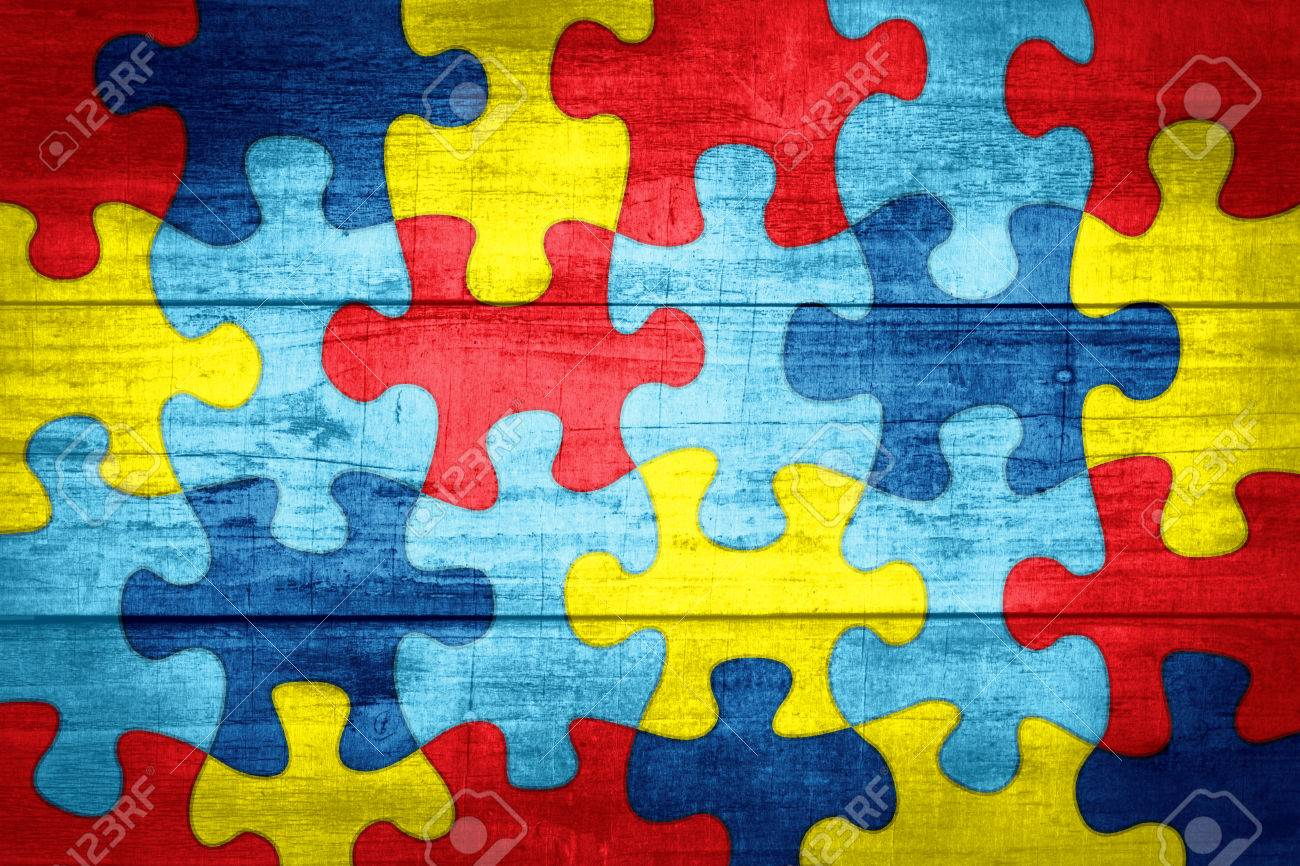 A Colorful Autism Awareness Puzzle Background With Wood Texture 1300x866