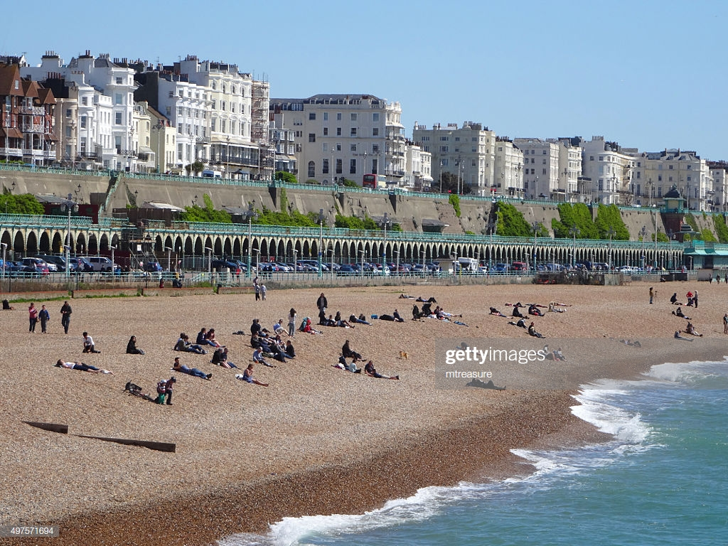 Image Of Sunbathers On Brighton Beach In Spring Background Hotels 1024x768