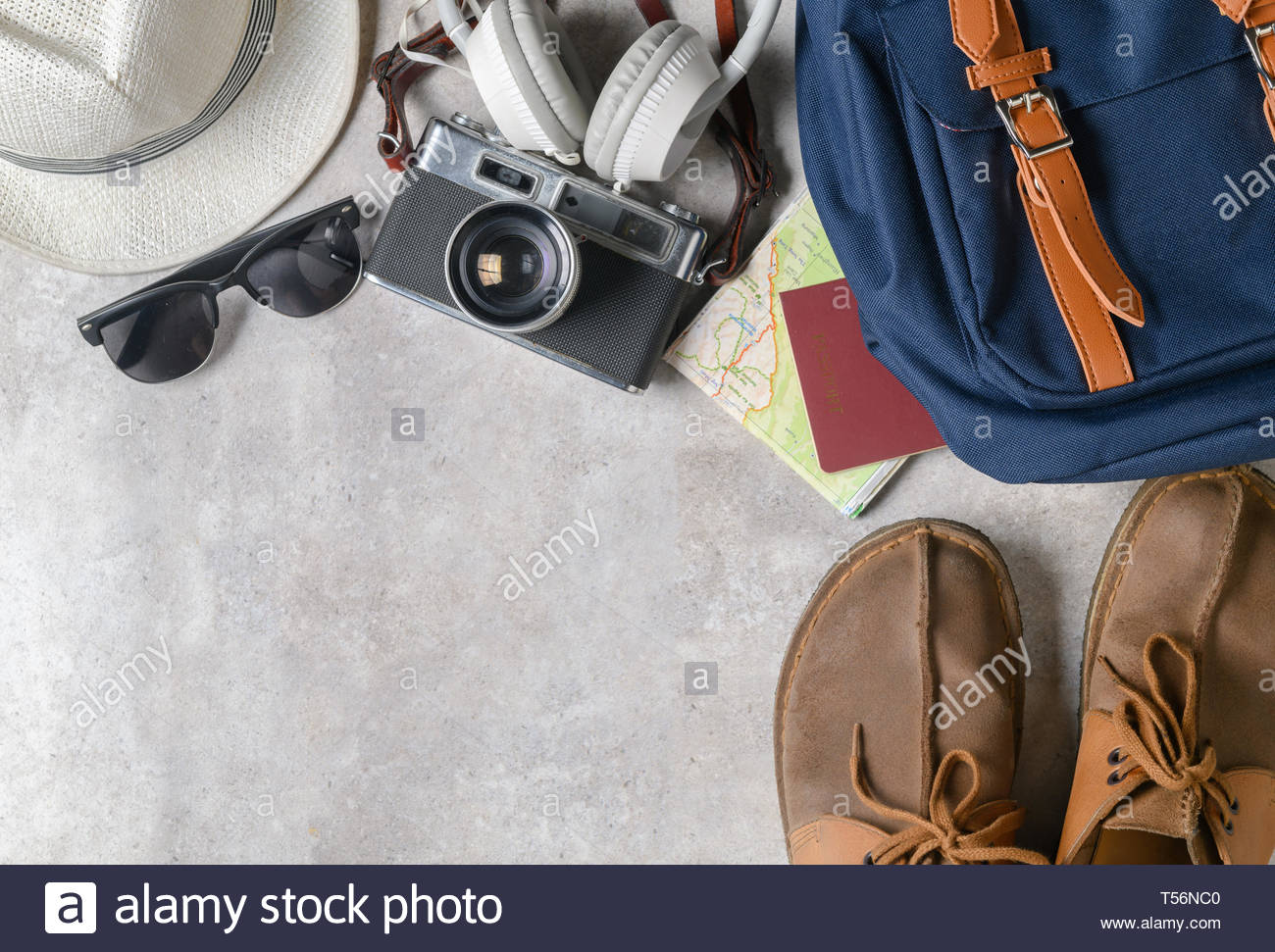 prepare backpack accessories and travel items on marble background 1300x971
