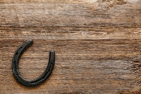 Old Metal Horseshoe on Antique Wood Background   Stock Photo 590x393