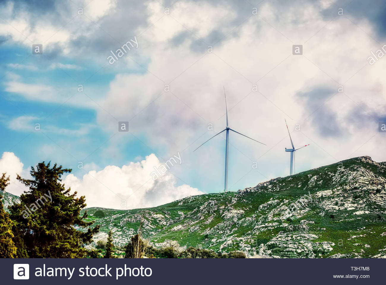 Wind turbines on the mountaintop against a cloudy sky background 1300x959