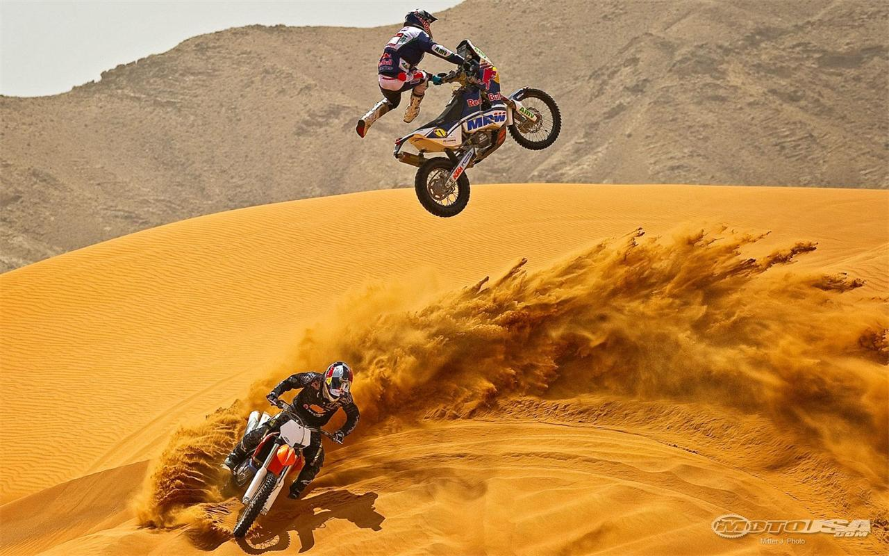 KTM Dakar racer Mark Coma doing freestyle on his rally bike alongside 1280x800