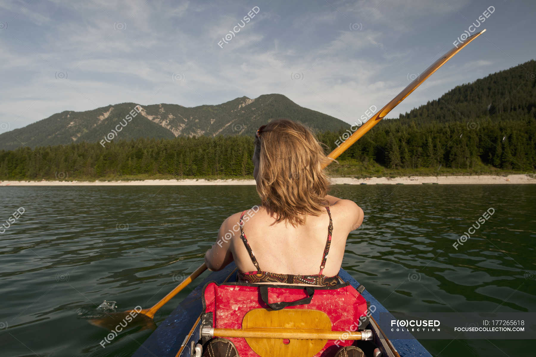 Rear view of woman paddling canoe over mountain range on 1800x1198