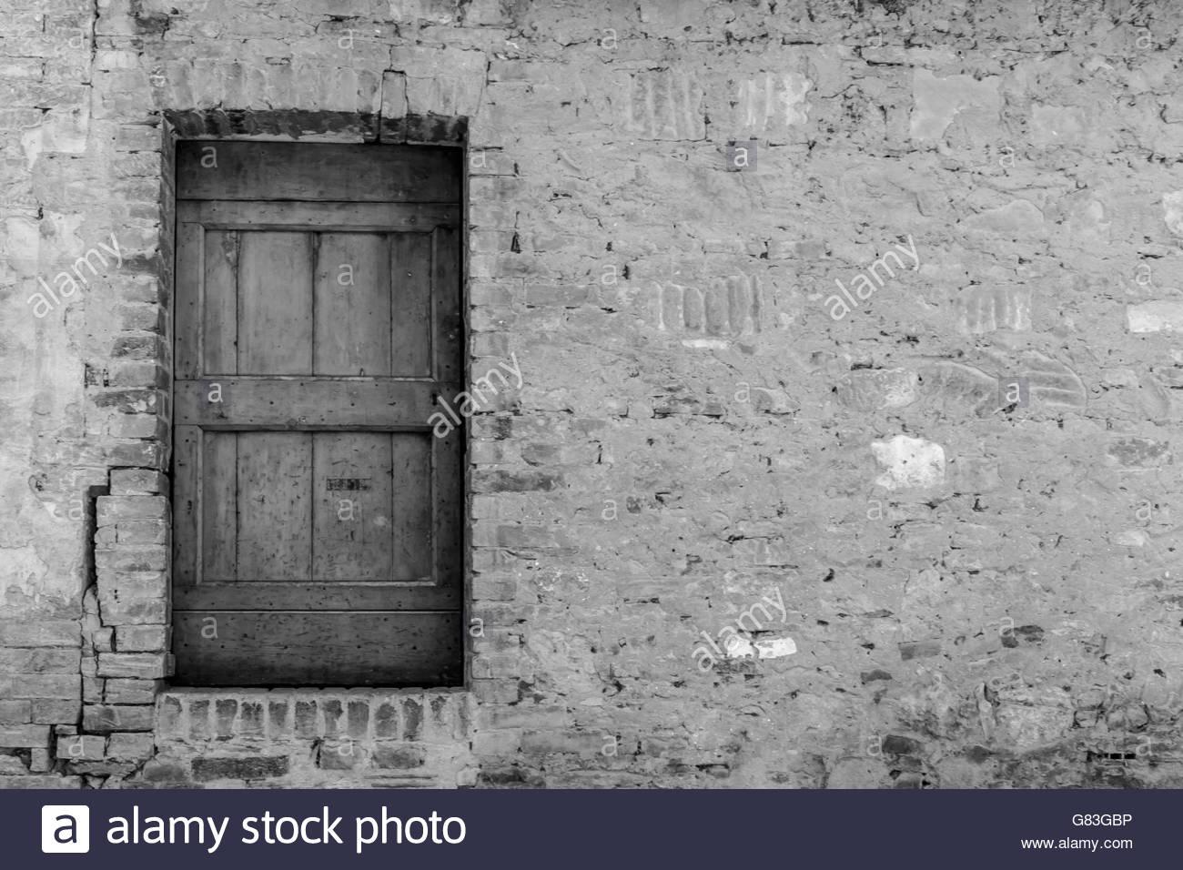 Rustic wooden door in black and white in random stonework Stock 1300x956