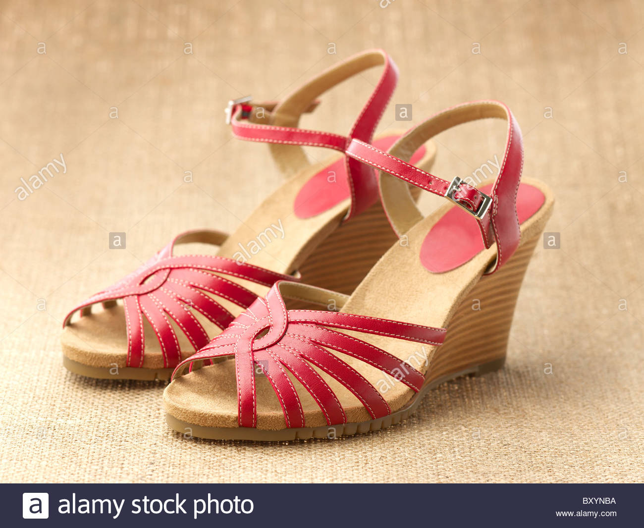pair of red womens shoes sandals on a raffia background Stock 1300x1066