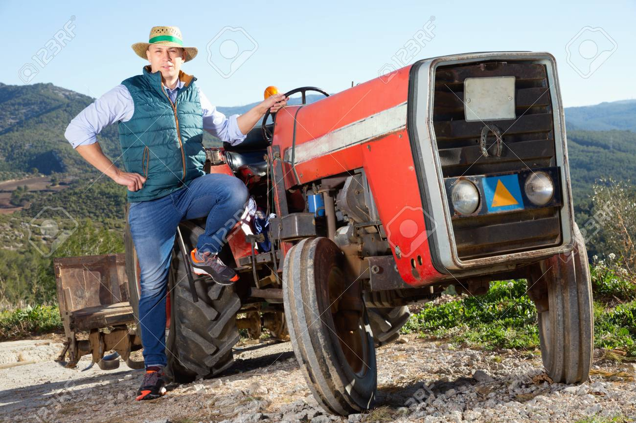 Portrait Of Adult Glad Positive Male Farmer Near Tractor On 1300x866