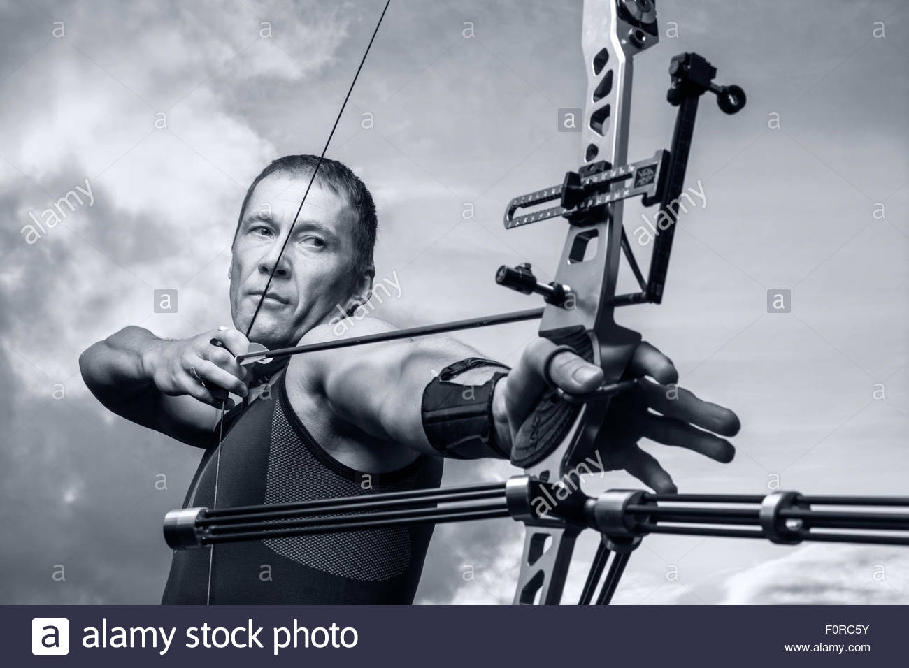 Tough man with bow and arrows close up with cloudy sky at Stock 1300x956