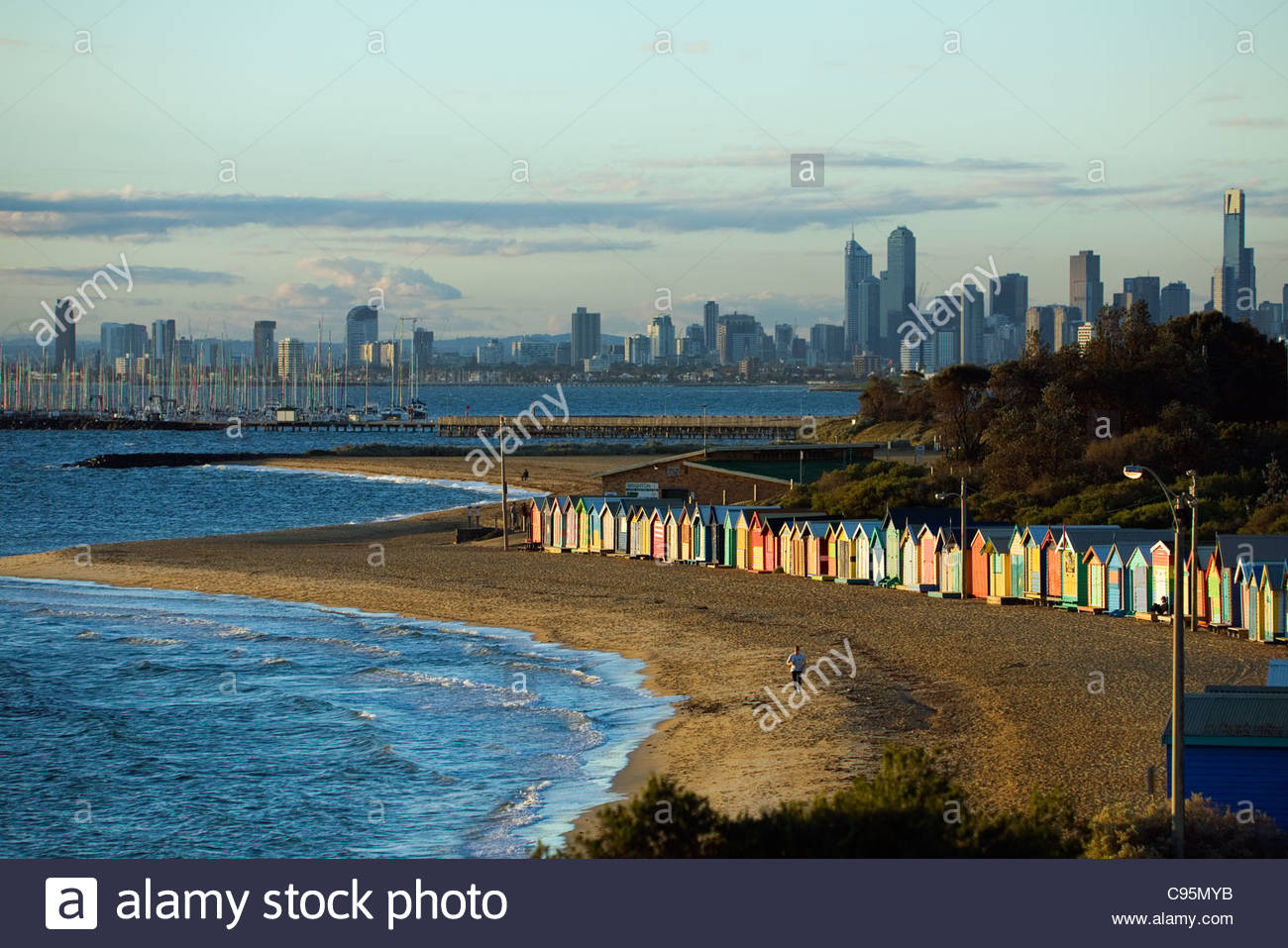 View of beach huts at Brighton Beach with city skyline in 1300x957