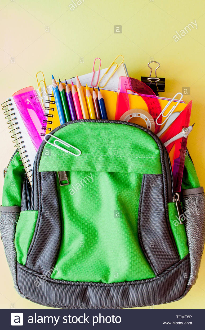 Flat lay composition with backpack and school stationery on yellow 866x1390