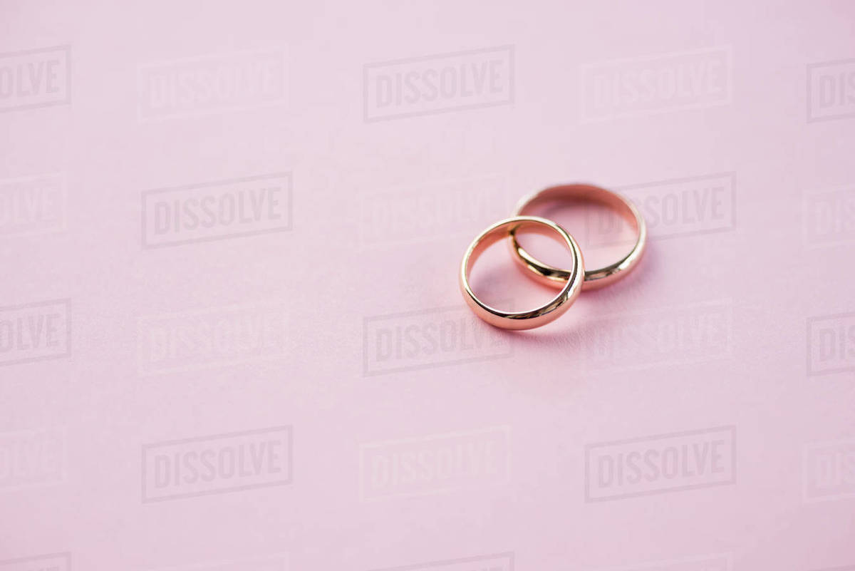 Close up view of shiny golden wedding rings on pink wedding rings 1200x801