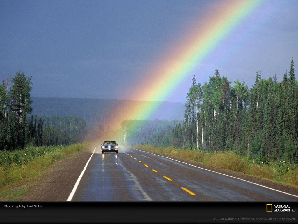 the end of a rainbow spotlights a solitary car traveling down a 1024x768