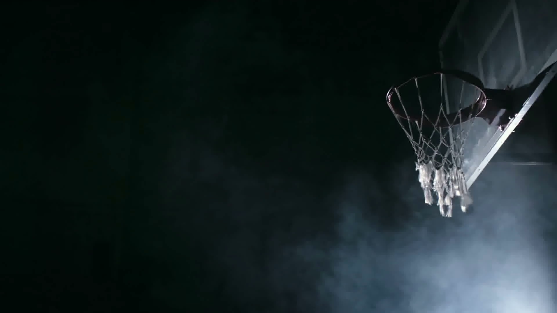 One handed slam dunk performed by basketball player in dark court 1920x1080