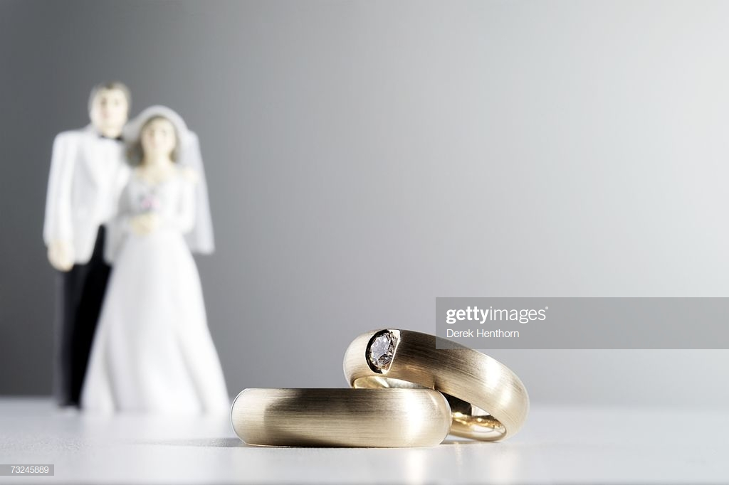 Two Wedding Rings Bride And Groom Figurines In Background High Res 1024x682