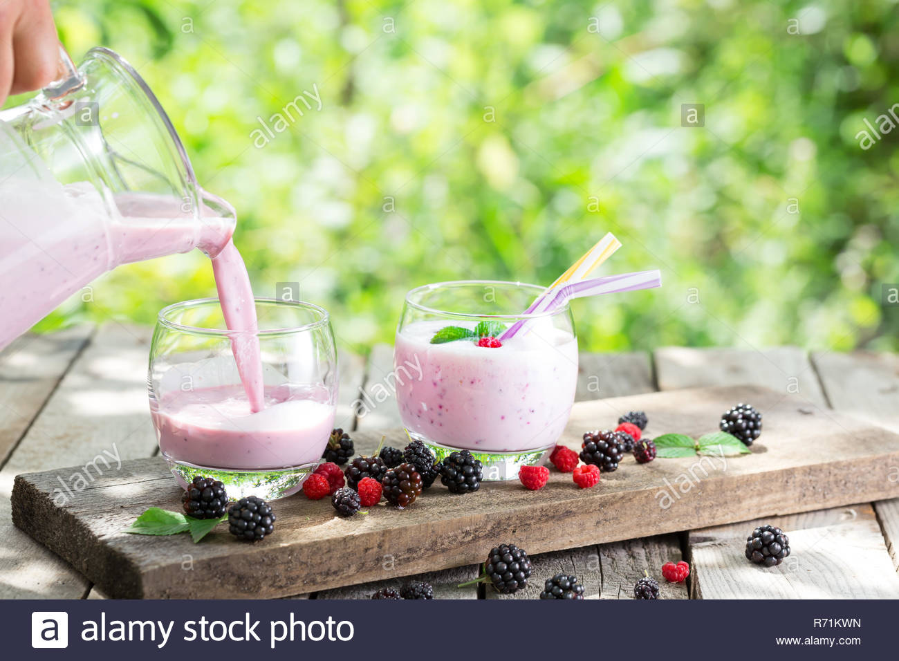 Berry smoothie or yogurt pouring from jug into glass against the 1300x956