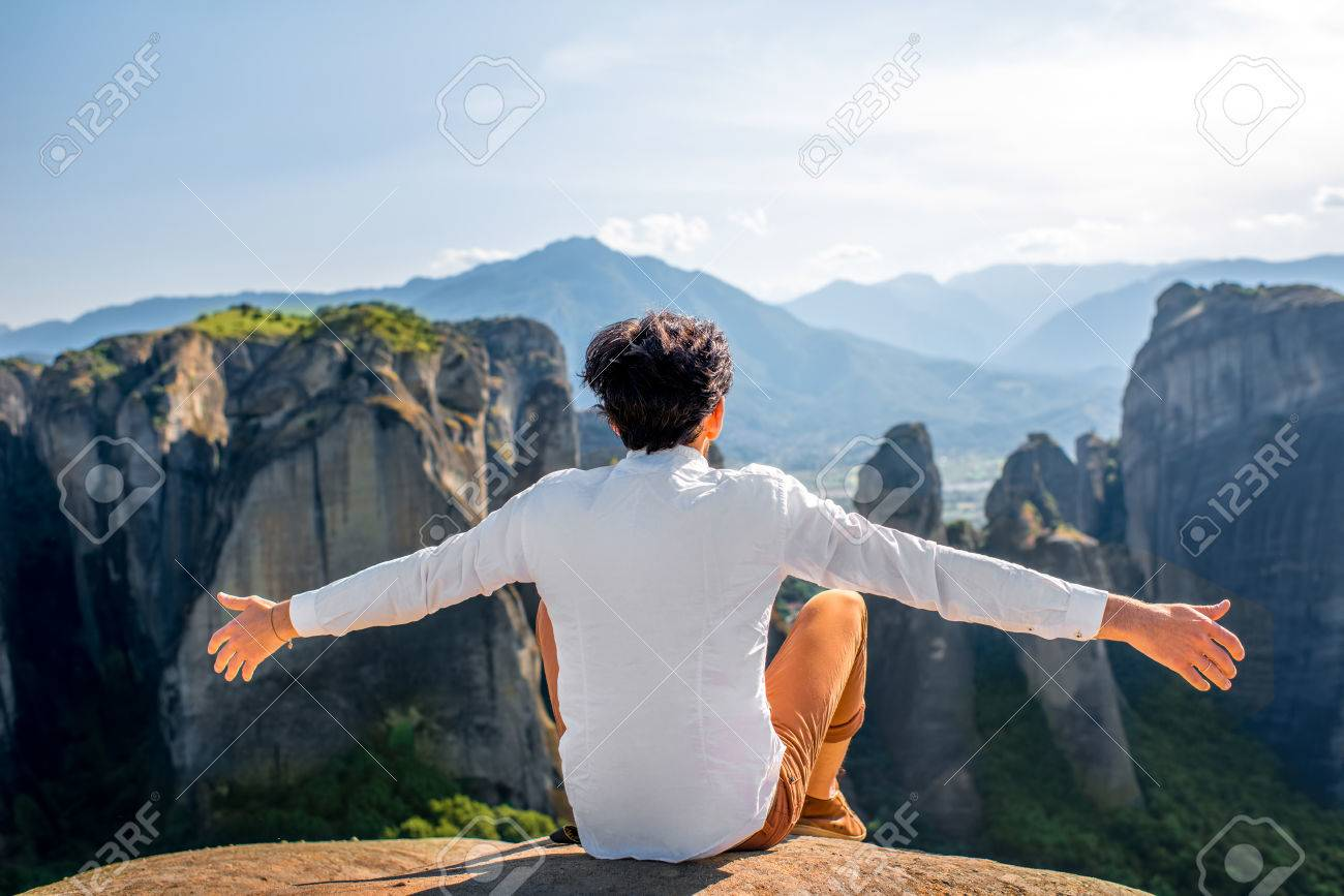 Well dressed Man Sitting On The Rocky Mountain On Beautiful Scenic 1300x867