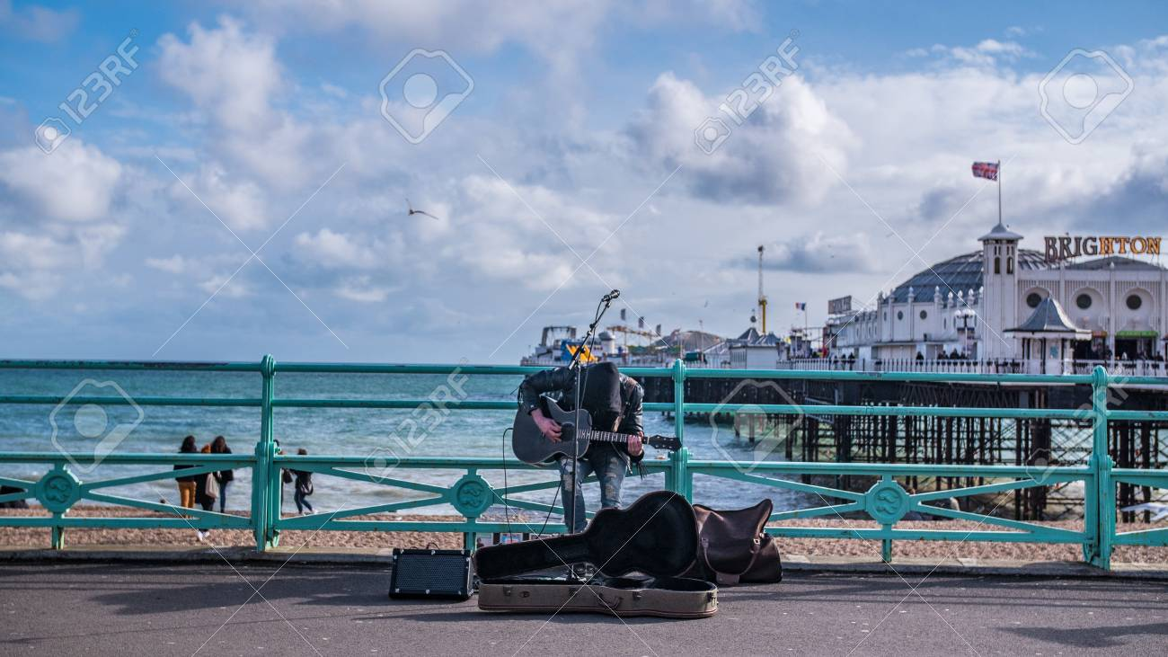 A Street Musician Playing Guitar And Singing With Brighton Pier 1300x731