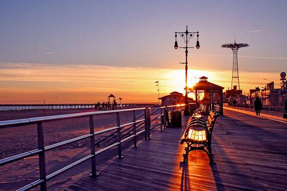 Coney Island boardwalk at Sunset with Parachute Jump in the background 585x390