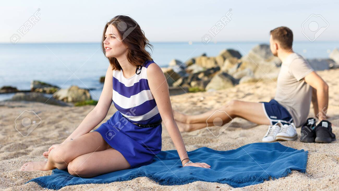 Glad Girl Sitting On The Beach Man On The Background Stock Photo 1300x732