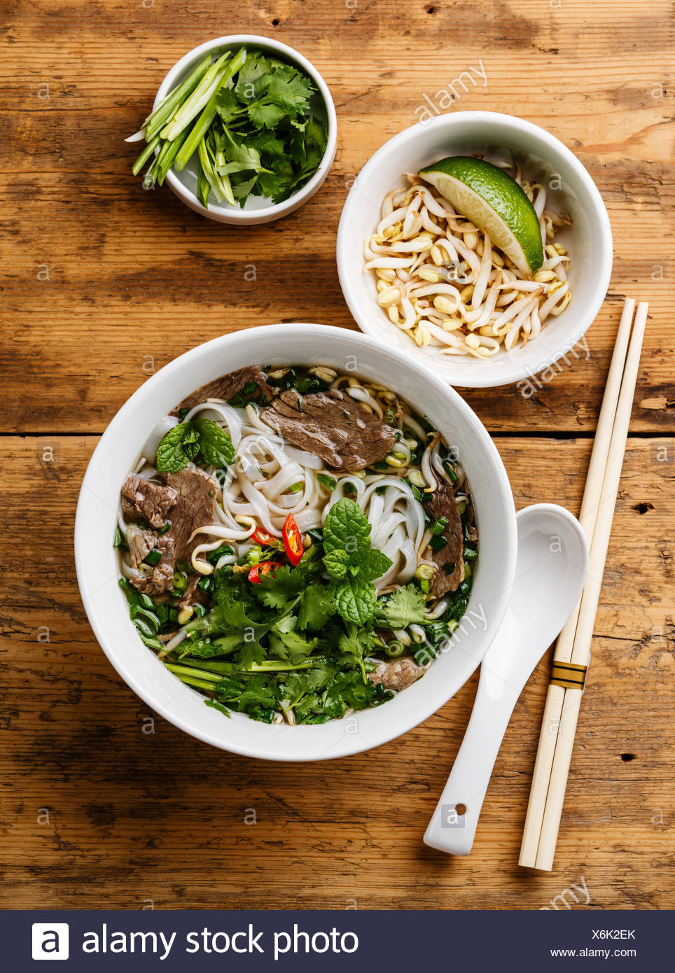 Pho Bo vietnamese Soup with beef and soybean seedlings on wooden 964x1390