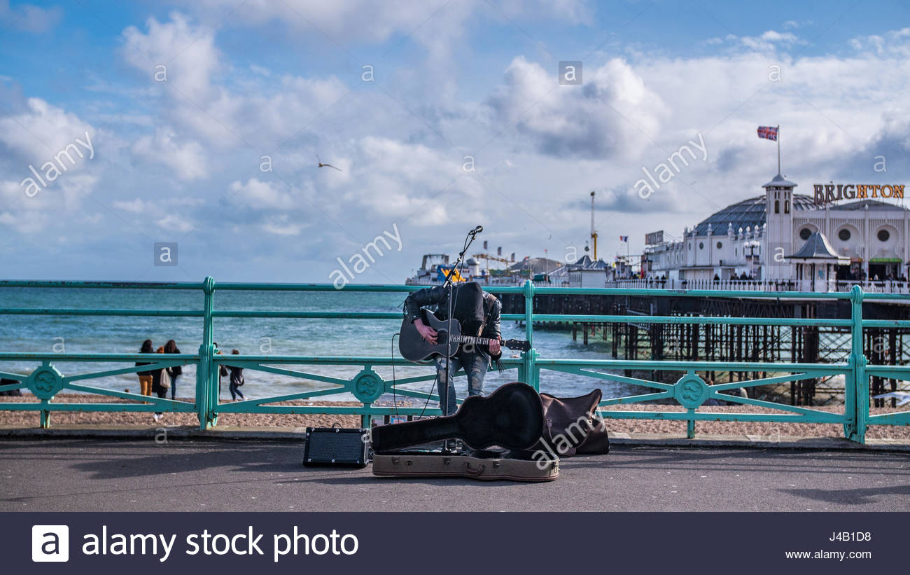 A street musician playing guitar and singing with Brighton pier 1300x821