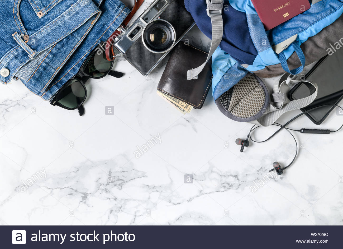 prepare backpack accessories and travel items on marble background 1300x942