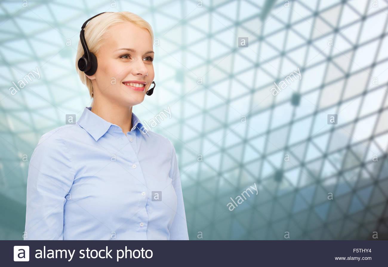 helpline operator in headset over grid background Stock Photo 1300x897