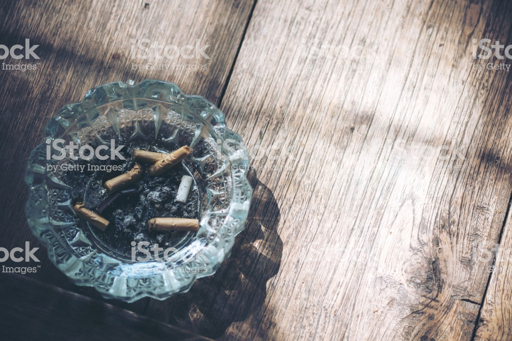Cigarette Stub In A Glass Ashtray On Wooden Table Background Stock 1024x683