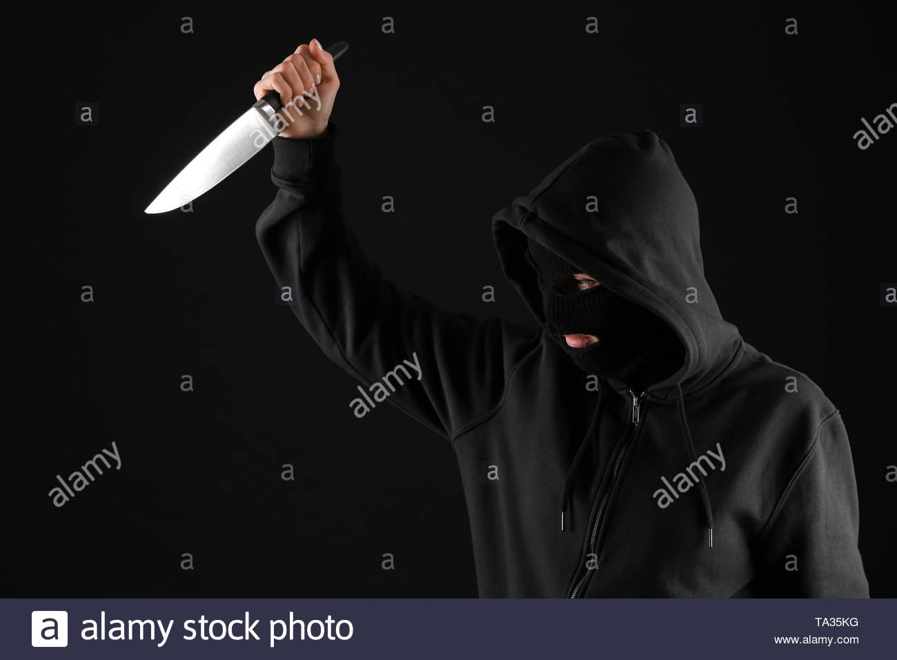 Bandit with knife on dark background Stock Photo 247162036   Alamy 1300x956