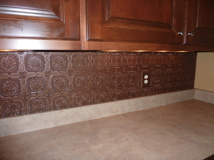 Textured wallpaper backsplash painted with aged copper paint 736x552