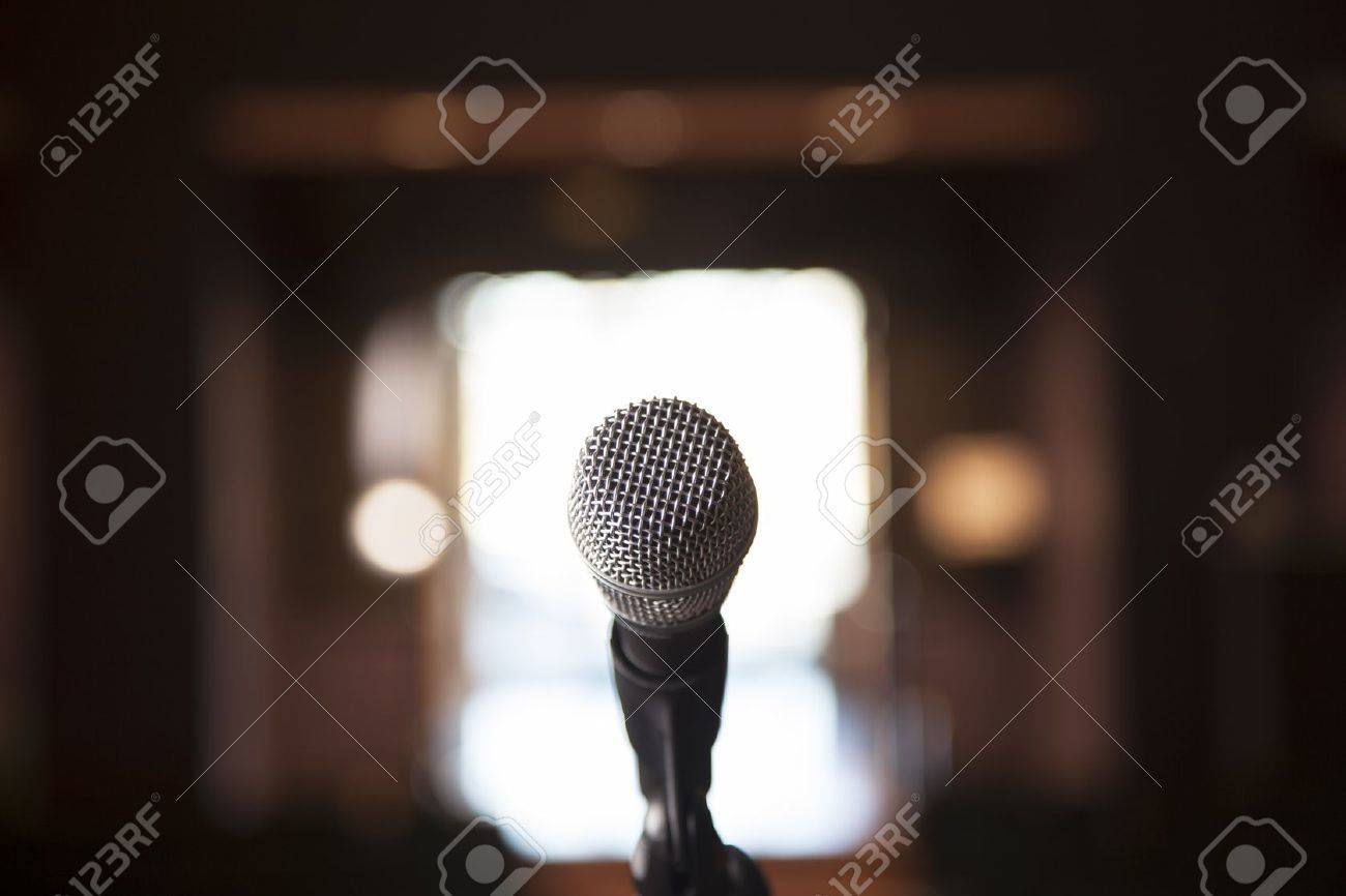 A Microphone Sits On A Stand With Bright Bocca In The Background 1300x866