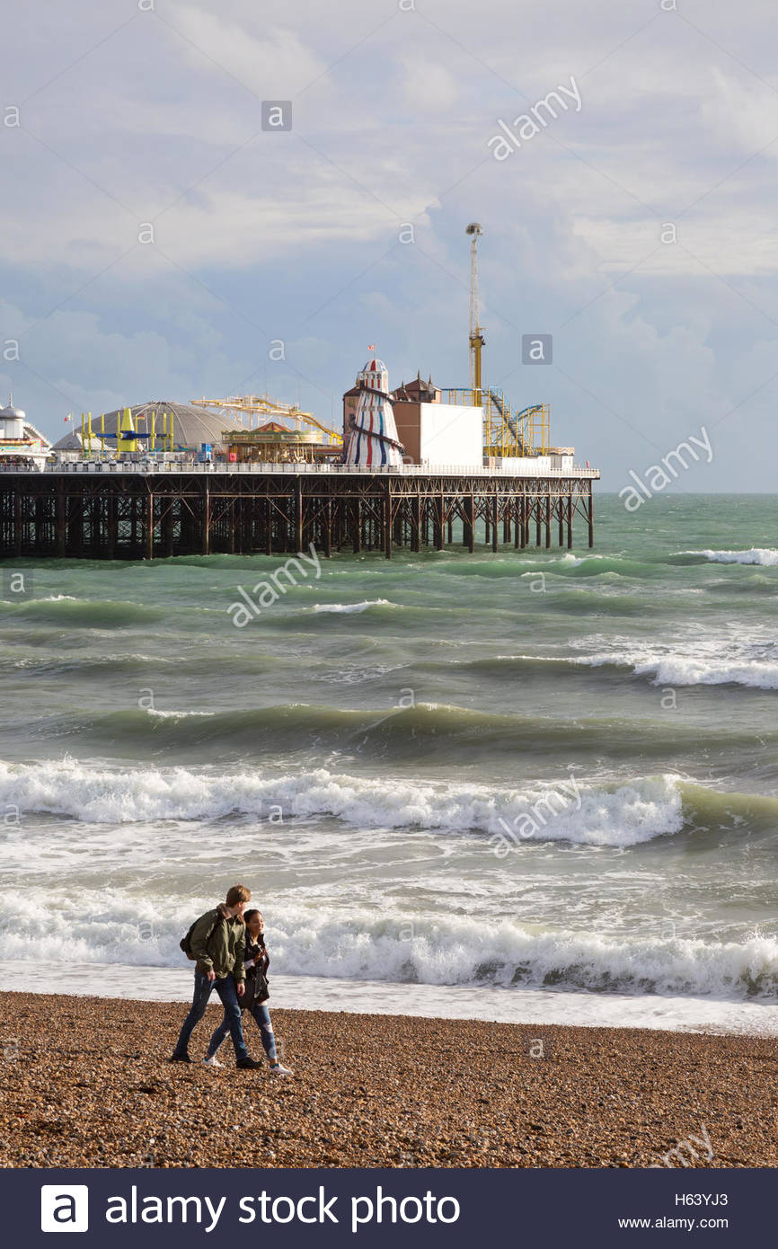 A couple walking on Brighton beach Brighton Pier in the 866x1390