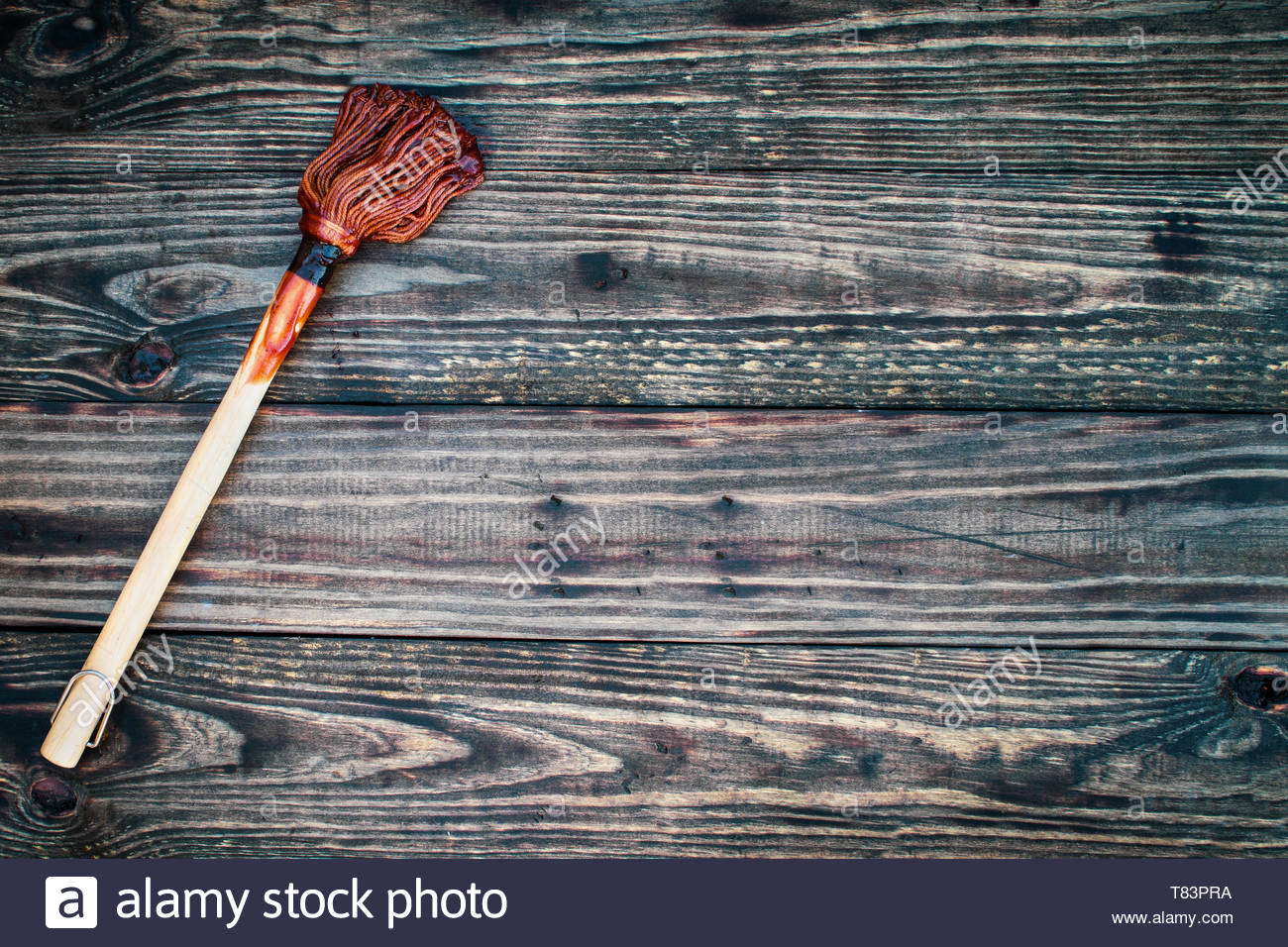 BBQ Mop or brush over top a rustic wood table background with 1300x956
