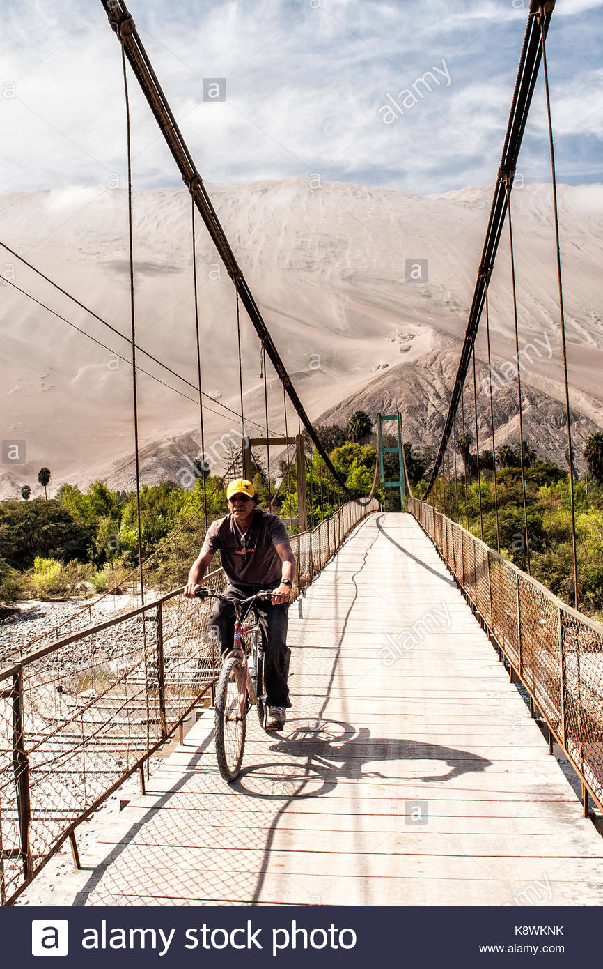 Man riding a bike on a footbridge and Cerro Toro Mata in the Stock 866x1390