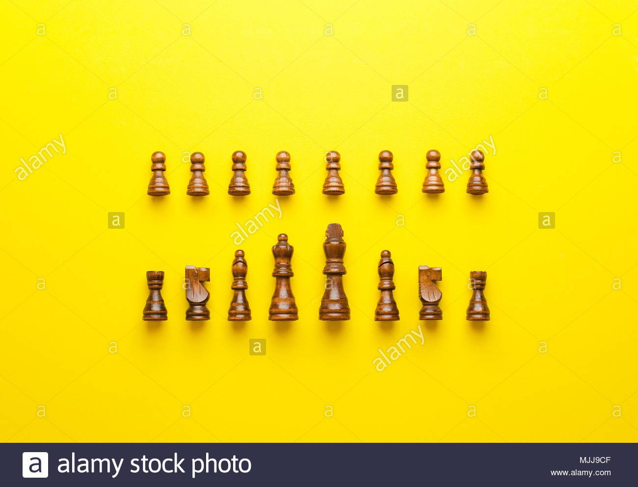 Wooden chess figurines organized in a row over yellow background 1300x992