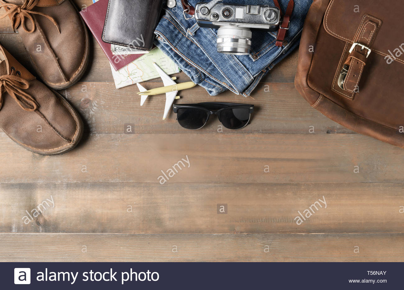 prepare backpack accessories and travel items on wood background 1300x936