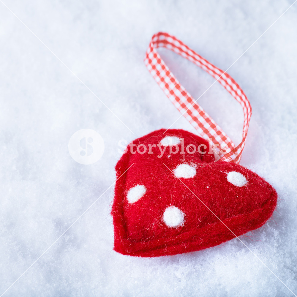 Red toy suave heart on a frosty white snow winter background 1000x1000