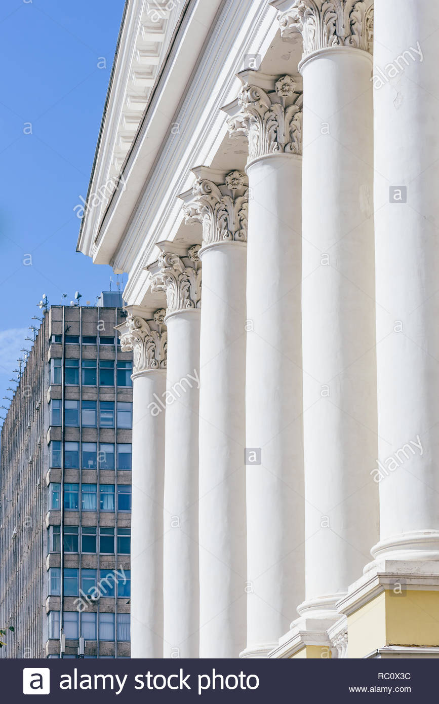 Front of Old Buildig with Columns and Skyscrapper on Background 867x1390