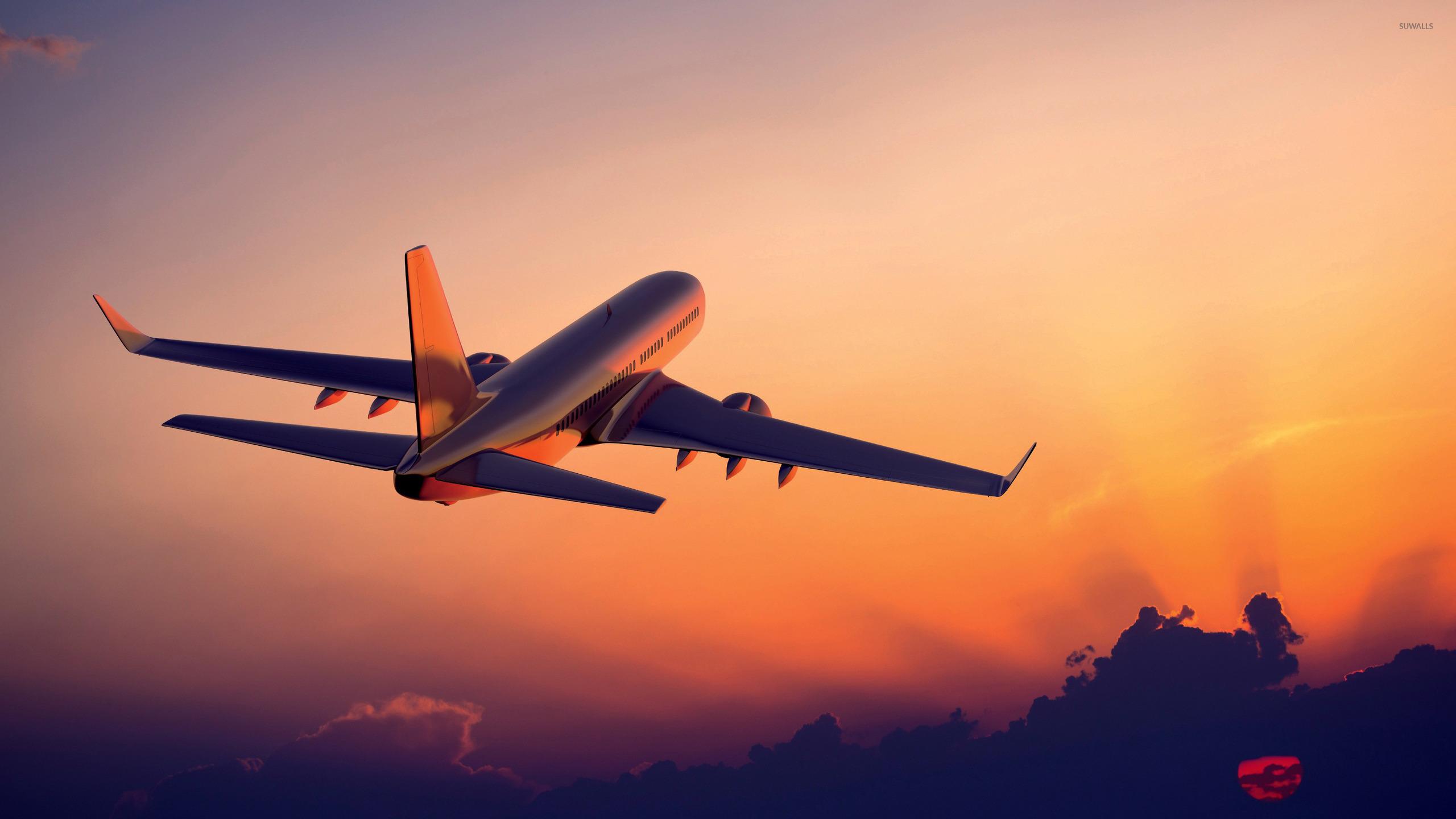 Passenger aircraft flying towards the sunset light wallpaper 2560x1440
