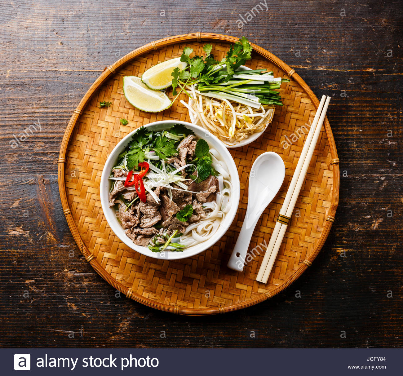 Pho Bo vietnamese Soup with beef on bamboo tray on wooden 1300x1213
