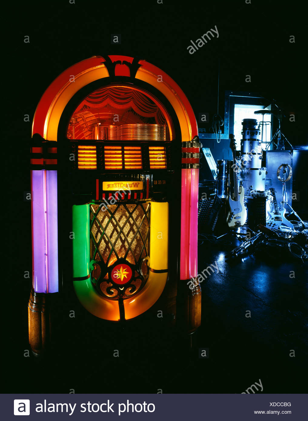 Still life with a jukebox in the foreground and a stack of musical 1017x1390