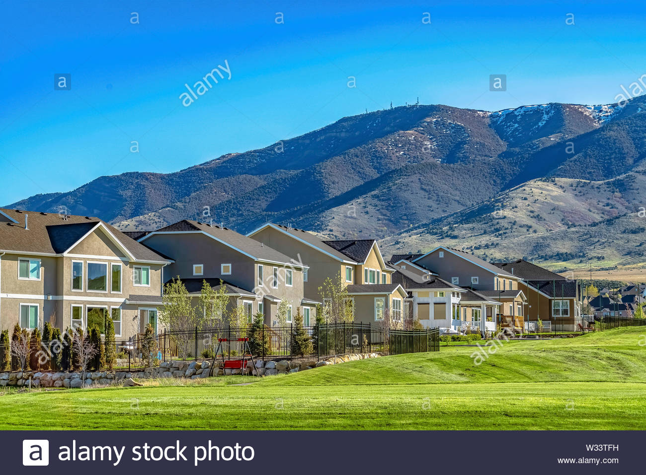 Multi storey homes with towering mountain and blue sky background 1300x957