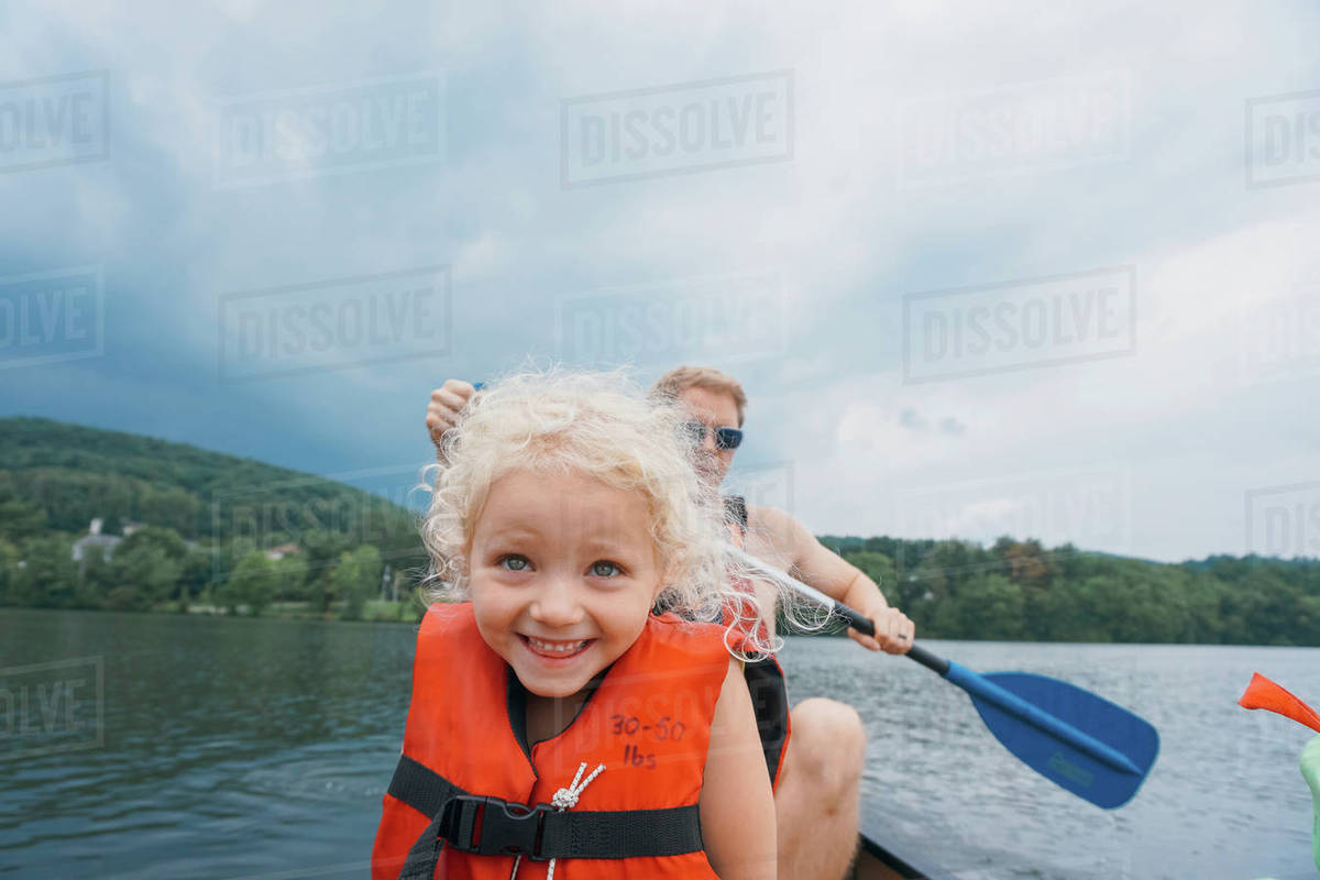 Happy daughter in canoe with father canoeing in background against 1200x800