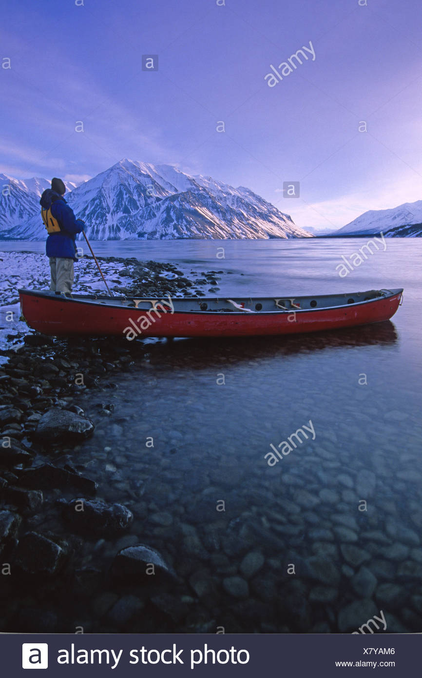 Hiker beside Canoe in Winter with St Elias Mountains in the 866x1390