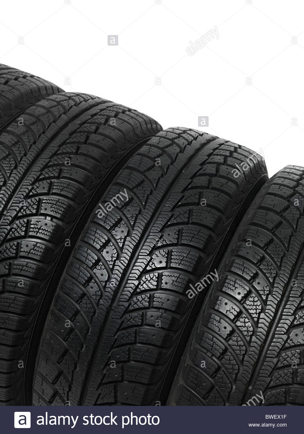 Set of four winter tires isolated on white background Stock Photo 975x1390