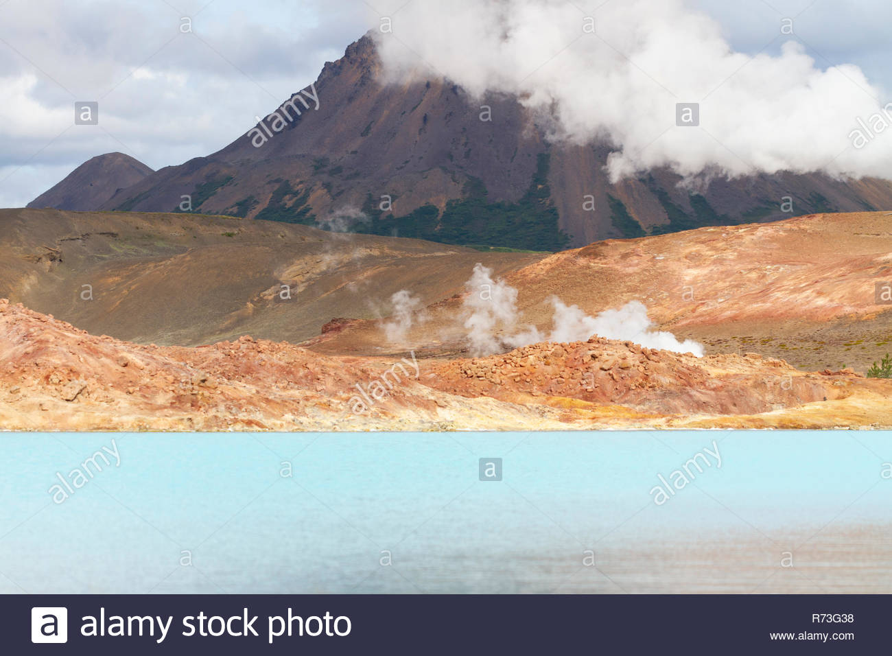 blue geothermal lake in volcanic zone with the cone of a volcano 1300x956